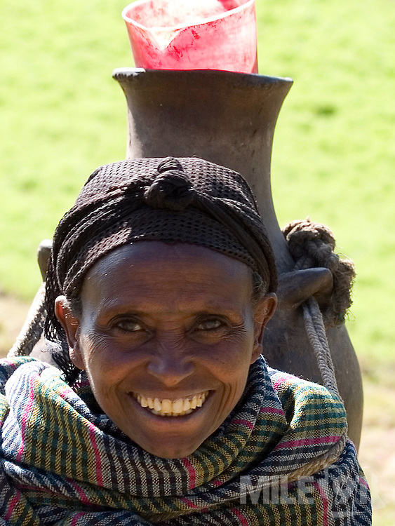Women collecting water from a capped spring near their village in Kotoba, Ethiopia. Capping the spring has helped improve access and the quality of the water.