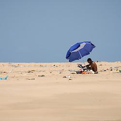 Pessoa a ler jornal debaixo de uma sombrinha no meio de lixo depositado pelas ondas nos bancos de areia do Mussulo. Angola