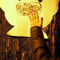 A woman touches a paper cut out angel of victims as community members gather for a candlelight vigil in honor of Sandy Hook Elementary School Principal Dawn Hochsprung on December 18, 2012, in Naugatuck, CT, 4 days after a mass shooting of 20 children and 7 adults at Sandy Hook Elementary School.