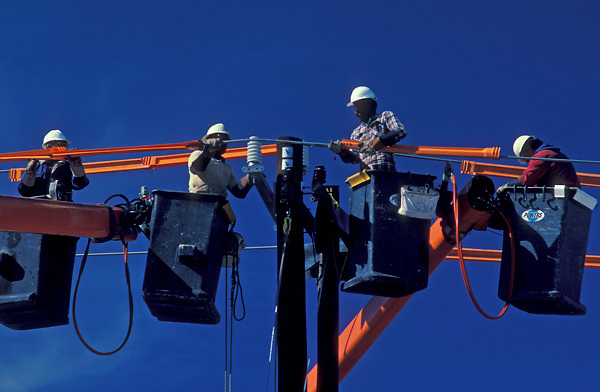 Stock photo of four men elevated and working on power lines