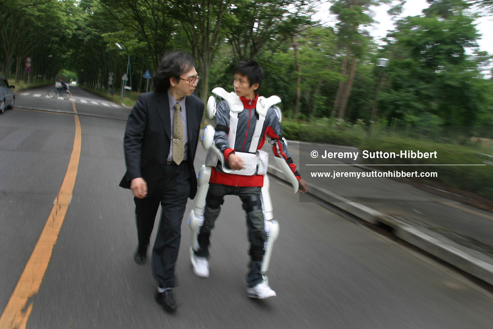 """Professor Yoshiyuki Sankai (on left), of the Cybernics Lab, University of Tsukuba, walks with a colleague wearing a prototype of the 'Cyberdyne HAL Robotsuit', in the university grounds, in University of Tsukuba, Tokyo, Japan, on Wednesday, June 29, 2005. The suit is an """"exo-skeleton type power assist system"""" enabling the wearer to lift heavier weights than would be possible without the suit. """"Some sensors such as angle sensors, myoelectrical sensors, floor sensors etc. are adopted in order to obtain the condition of the HAL and the operator. All of the motordrivers, measurement system, computer, wireless LAN, and power supply are built in the backpack. Using the battery attached on the waist, HAL works as a complete wearable system""""."""
