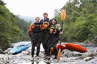Three people with kayaks by river portrait