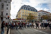 Pedestrians cross a road on the 29th of October 2019 as a tram passes through a busy Luís de Camões square, Lisbon, Portugal.  (photo by Andrew Aitchison / In pictures via Getty Images)