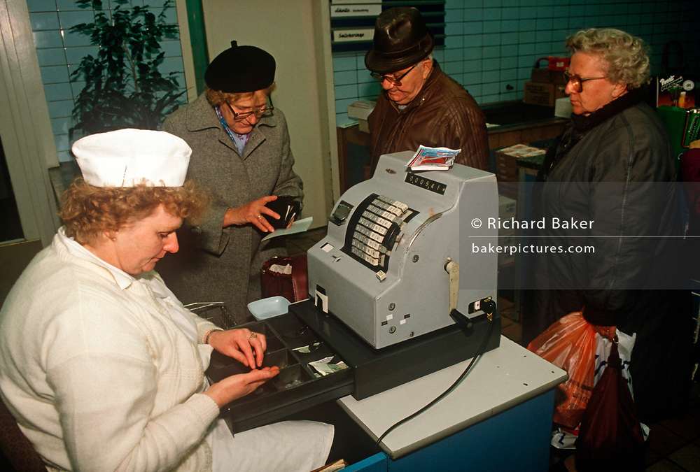 As a staff member counts coins, 1990s women shoppers gather around the till to pay cash in a Budapest shop, on 13th June 1990, in Budapest, Hungary. (Photo by Richard Baker / In Pictures via Getty Images)