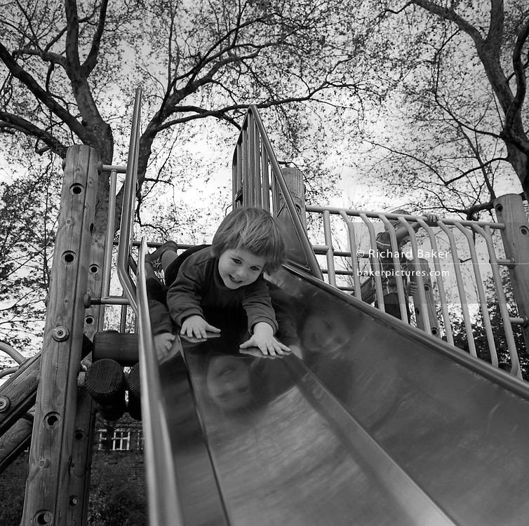 With hands outstretched and a nervous smile on her face, a 3 year-old goes head first down a slide in her local park in south London.