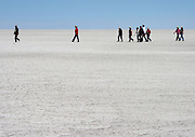 Tourists walk across the salt on the Salar de Uyuni, the world's largest salt flat, just outside of the town of Uyuni on Bolivia's Altiplano, at just over 3,600 metres above sea level