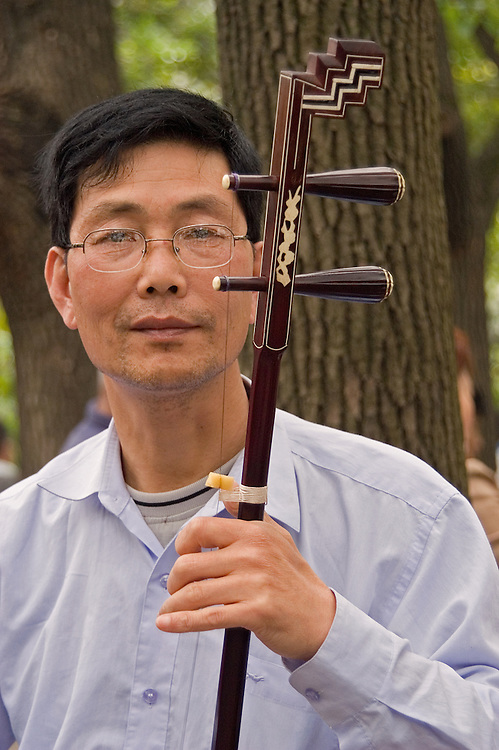 A man entertains a crowd in the park with his Erhu.
