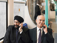 Businessmen sitting on commuter train Using Cell Phones