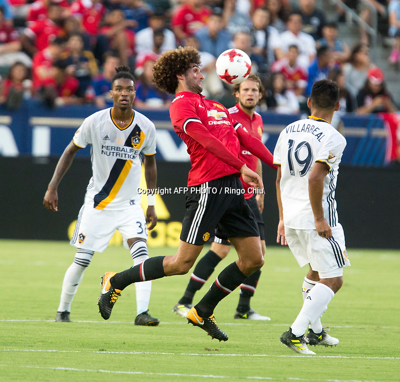 Manchester United Marouane Fellaini, center, controls the ball against Los Angeles Galaxy during the first half of a national friendly soccer game at StubHub Center on July 15, 2017 in Carson, California.   AFP PHOTO / Ringo Chiu