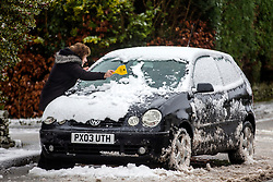 © Licensed to London News Pictures. 13/02/2020. Shap UK. A lady clears snow from her car in the village of Shap in Cumbria as the UK braces for more bad weather over the weekend. Photo credit: Andrew McCaren/LNP