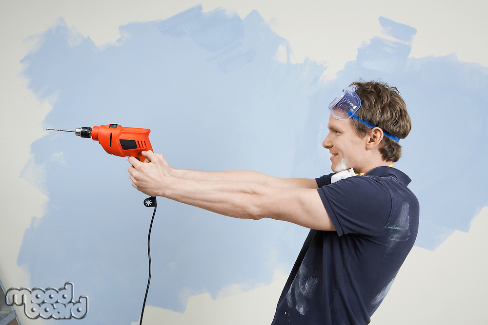 Man pointing drill in front of half painted wall side view