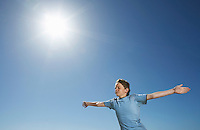 Boy with arms outstretched half length in front of blue sky