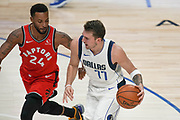 Dallas Mavericks point guard Luka Doncic (77) brings the ball down while being guarded by Toronto Raptors guard Norman Powell (24) during an NBA basketball game, Saturday, Nov. 16, 2019, in Dallas. The Mavericks defeated the Raptors 110-102. (Wayne Gooden/Image of Sport)