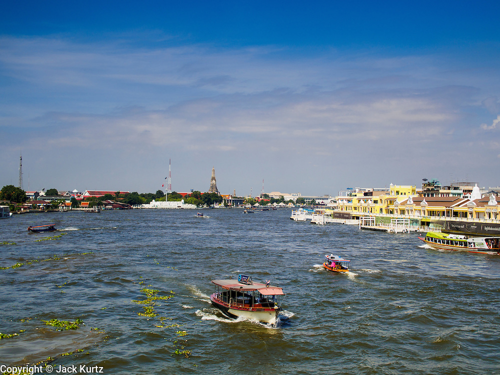 "28 OCTOBER 2014 - BANGKOK, THAILAND:   Passenger boats on the Chao Phraya River pass the Yodpiman Flower Market, also known Pak Khlong Talat, in Bangkok. The market is being renovated and gentrified as a ""heritage mall."" The first phase of the renovation are the new yellow buildings along the river.    PHOTO BY JACK KURTZ"