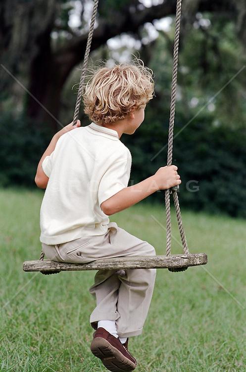 boy sitting on a rope swing in a grassy backyard
