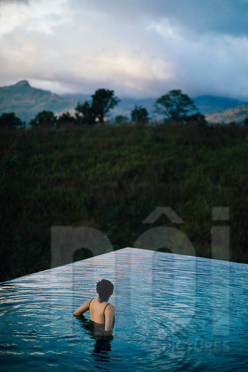 A woman in a resort pool looking out over the mountains, Kandy, Sri Lanka, Asia