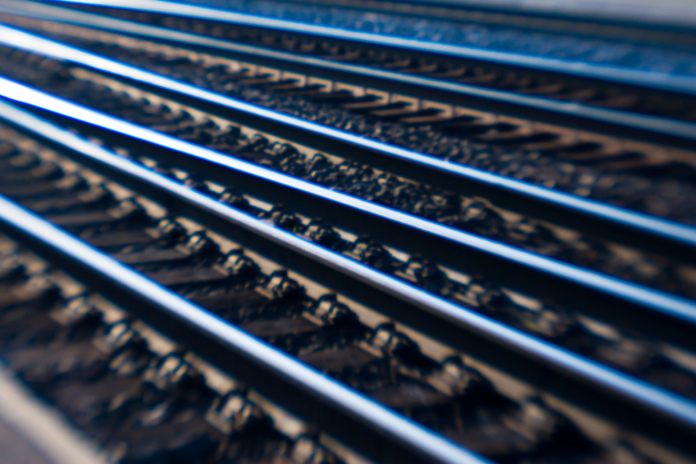 Seen through a Lensbaby, a complex maze of railroad track reflects late afternoon sunshine.