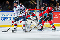 KELOWNA, CANADA - OCTOBER 27: Kyle Olson #25 of the Tri-City Americans looks for the pass while back checked by Cal Foote #25 in front of the net of James Porter #1 of the Kelowna Rockets on October 27, 2017 at Prospera Place in Kelowna, British Columbia, Canada.  (Photo by Marissa Baecker/Shoot the Breeze)  *** Local Caption ***