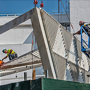 Workers assembling 18-foot white canopy sculpture. <br />