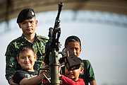 "11 JANUARY 2014 - BANGKOK, THAILAND: Thai children and a Thai soldier stand behind a machine gun on top of a vehicle during Children's Day in Bangkok. The Royal Thai Army hosted a ""Children's Day"" event at the 2nd Cavalry King's Guard Division base in Bangkok. Children had an opportunity to look at military weapons, climb around on tanks, artillery pieces and helicopters and look at battlefield medical facilities. The Children's Day fair comes amidst political strife and concerns of a possible coup in Thailand. Earlier in the week, the Thai army announced that movements of armored vehicles through Bangkok were not in preparation of a coup, but were moving equipment into position for Children's Day.      PHOTO BY JACK KURTZ"