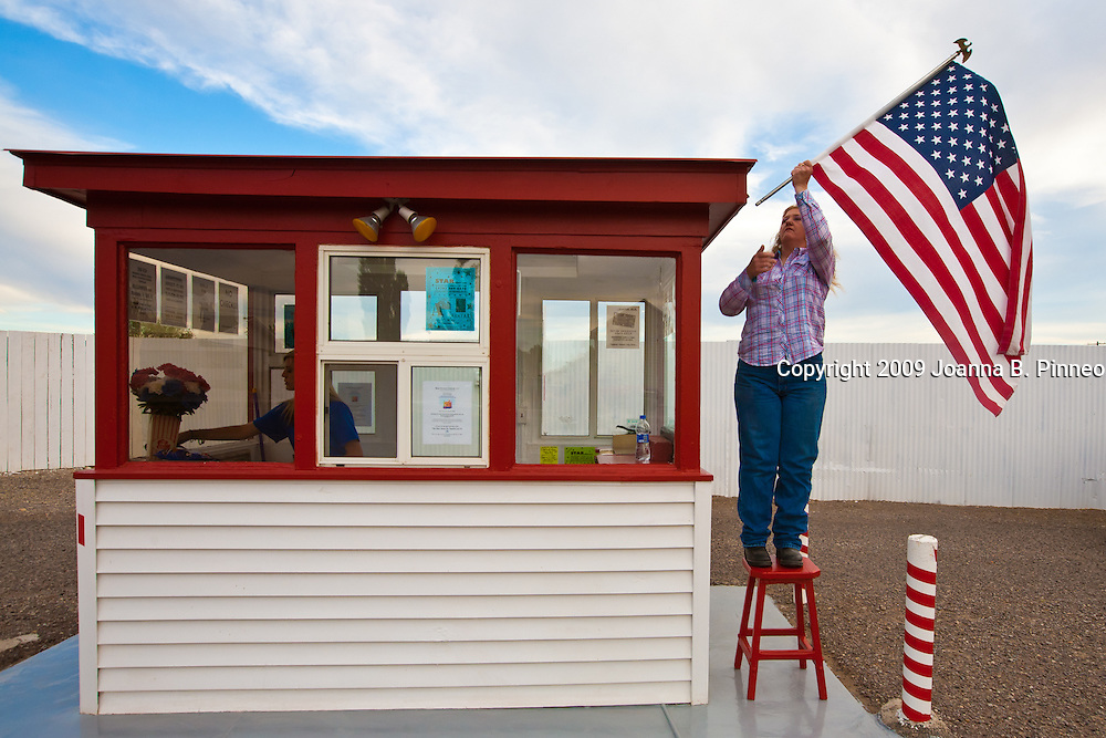 April Mason, 38, is the third generation of the DeVries family to operate the Star Drive In. April hangs up the American flag while Chelsey Goble readies the ticket booth just before opening the Star Drive In for the evening's movies.  Montrose, Colorado.