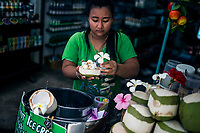 A vendor serves up fresh coconut ice cream to tourists at Lamai Beach in Koh Samui, Thailand.