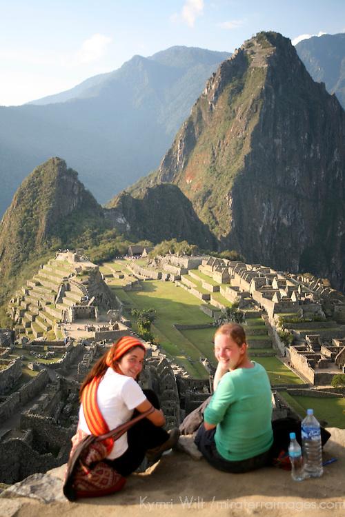 South America, Latin America, Peru, Machu Picchu. Two travellers overlooking the scenic citadel.