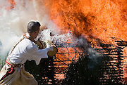 A mountain priest from the Shingo sect  of Buddhism douses with buckets of water the flames of a fire used in a purification ritual at Mt. Takao near Tokyo, Japan on March 14 2010.