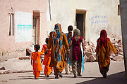 Indian women and girls dressed as wedding guests walking to the wedding in village of Rohet in Rajasthan, Northern India