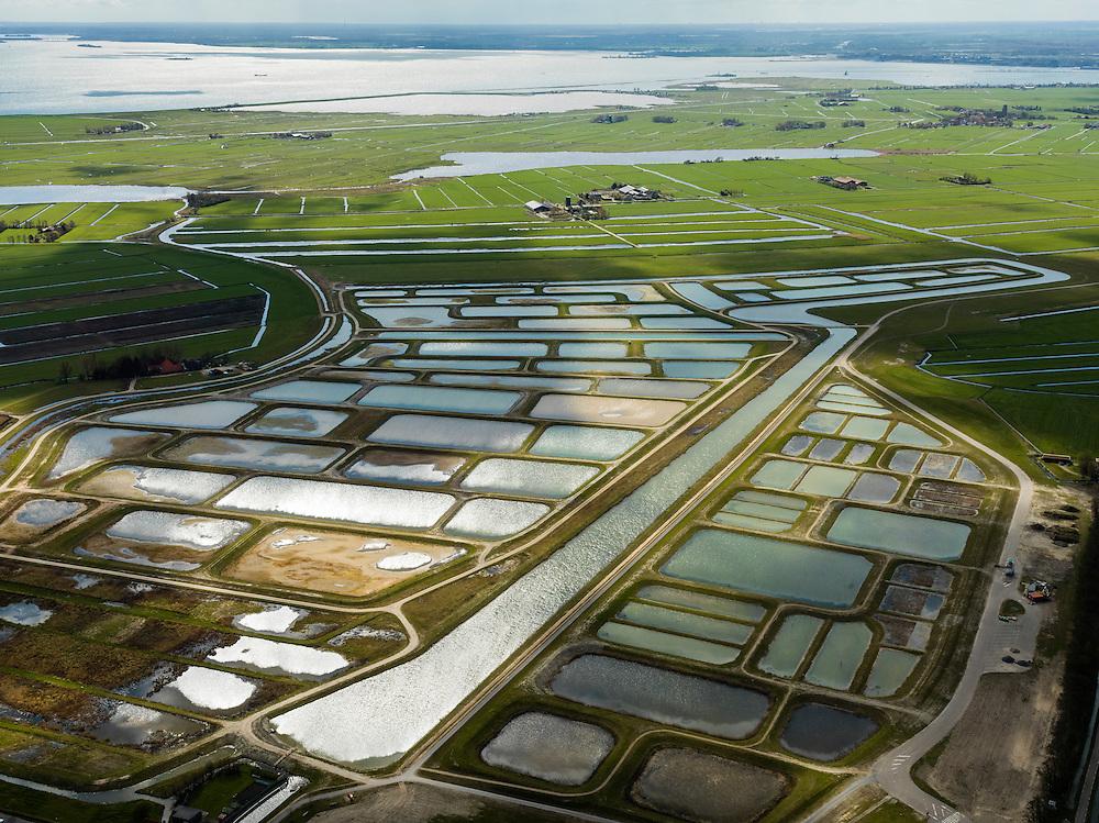 Nederland, Noord-Holland, Amsterdam (landelijk Noord), 16-04-2012; Waterland, Volgermeerpolder met daar achter Veenderij Zunderdorp, het water van de de Ransdorper Die, Kinselmeer en IJsselmeer..De Volgermeerpolder maakte oorspronkelijk ook deel uit van de Veenderij, tot in de jaren '50 is hier turf gewonnen. Na beeindiging van het vervenen werden de 'petgaten' volgestort met huisvuil en chemisch afval, onder andere met dioxine en benzeen afkomstig van Philips-Duphar..Inmiddels is de polder gesaneerd, de voormalige vuilstortplaats is afgedekt met folie en voorzien van en afdeklagen, bestaande uit zowel grond als ook water. Het ontwerp voorziet in een natuurgebied met 'sawa's' waarin nieuw veen zich kan ontwikkelen wat de vervuilde grond verder zal isoleren (natural capping)..The Volgermeerpolder in the rural area near Amsterdam once a landfill site for heavily polluted household and industrial waste, has been cleaned up using natural capping and turned into a nature area. .luchtfoto (toeslag), aerial photo (additional fee required);.copyright foto/photo Siebe Swart