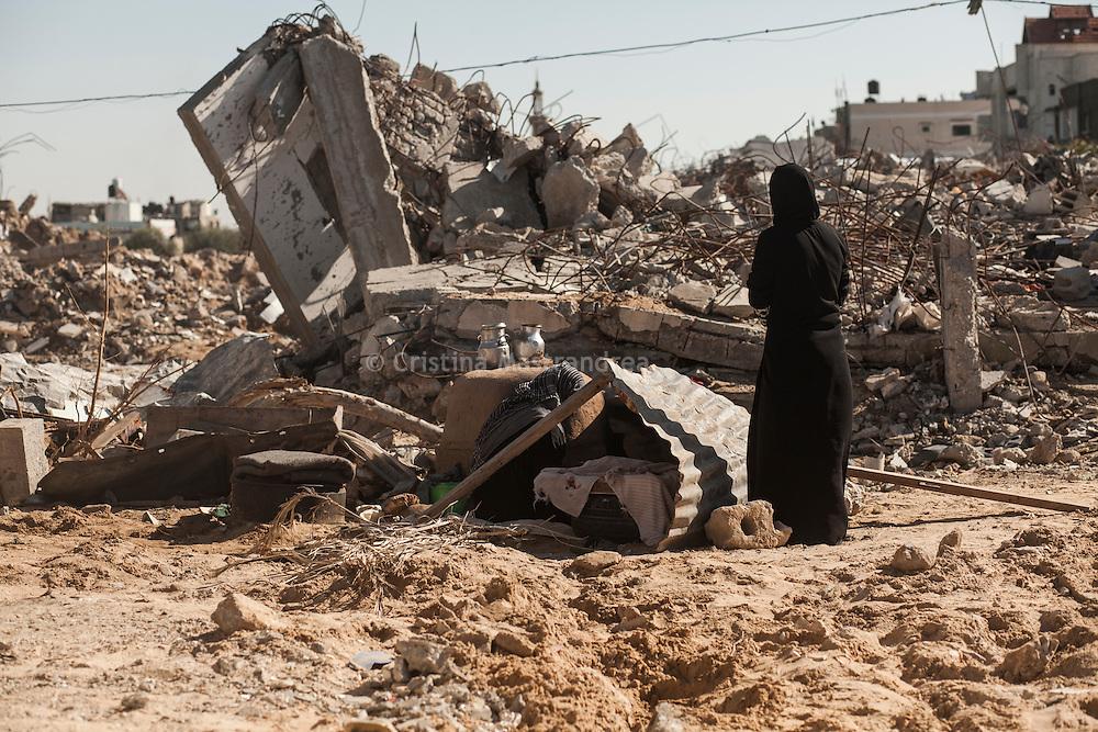 Kufha quartiere a sud della striscia di Gaza. Un'altra zone molto colpita dall'attacco israeliano &quot;Margine protettivo&quot;. Il quartiere &egrave; stato raso al suolo. La popolazione, a distanza di sei mesi dalla fine della guerra, vive tra le macerie della propria casa, al freddo, senza luce, gas e acqua. Molti dormono in container o in case improvvisate o dentro le macerie della loro casa.<br /> Nella foto una donna in piedi e un'altra seduta davanti ad un forno per fare il pane.