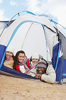 Four young adults lying down in small tent.