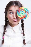 Young Asian woman holding a multicolored lollipop against white background