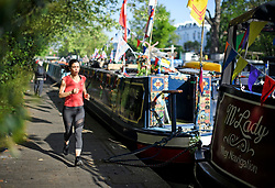 © Licensed to London News Pictures. 07/05/2018. London, UK. A jogger in the early morning sunshine at day three of the Canalway Cavalcade festival takes place in Little Venice, West London on Monday, May 7th 2018. Today is expected to be the hottest May bank holiday Monday on record. Photo credit: Ben Cawthra/LNP