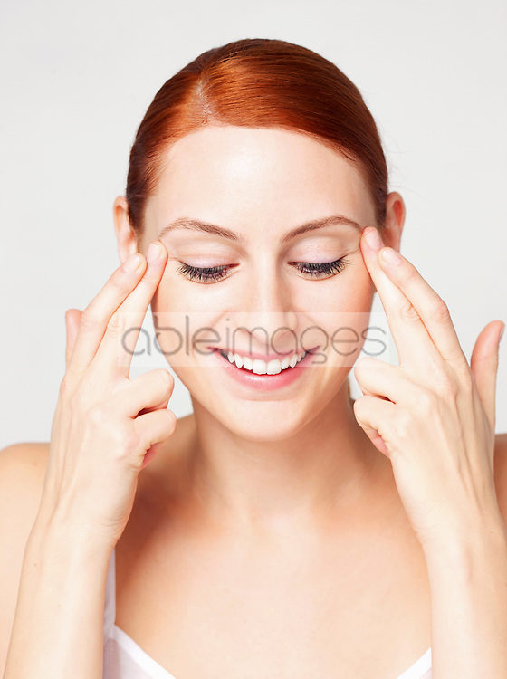 Woman with Fingertips on Corner of Eyes