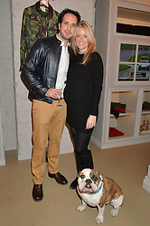 JAMES EDEN and his wife KATIE with their dog Brutus at the launch of the Private White VC flagship store, 73 Duke Street, London on 11th December 2014.