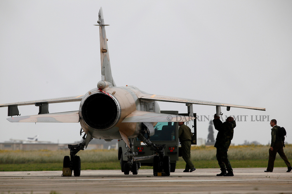 A Libyan Air Force Mirage F1 fighter jet is prepared for towing to a more secure part of Malta International Airport outside Valletta March 4, 2011.  The political asylum application of the two Libyan Air Force pilots who defected to Malta on February 21 is being considered and should be decided upon within weeks or months, according to a government spokesperson..REUTERS/Darrin Zammit Lupi (MALTA)