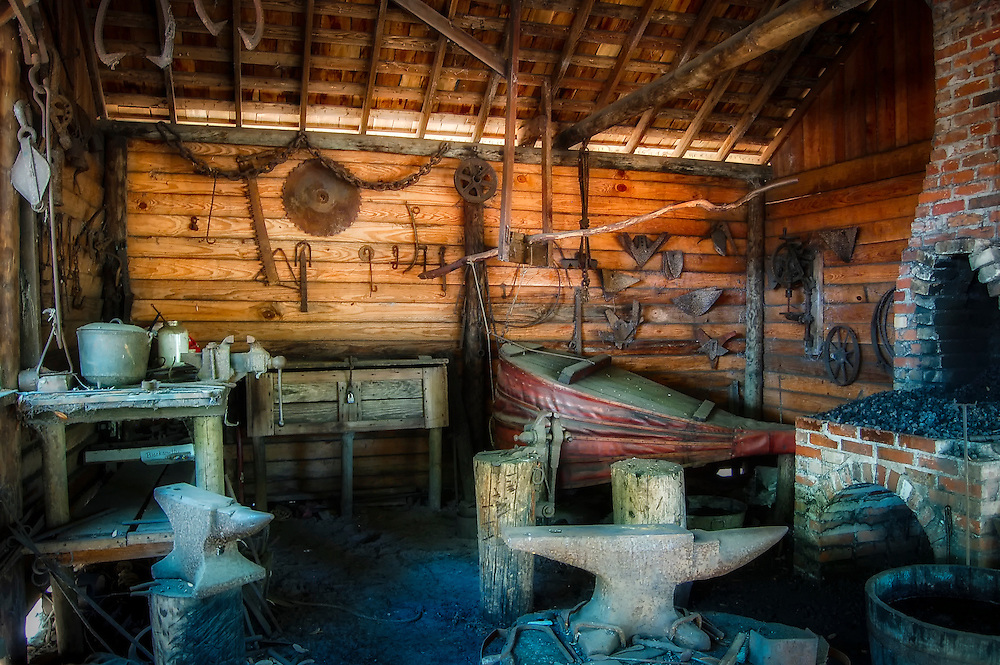 A blacksmith's shop complete with anvils, forge, bellows, and assorted tools.