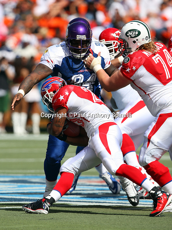 HONOLULU, HI - FEBRUARY 08: AFC All-Stars running back Marshawn Lynch #23 of the Buffalo Bills runs the ball while trying to avoid a tackle by defensive tackle Pat Williams #94 of the Minnesota Vikings of the NFC All-Stars in the 2009 NFL Pro Bowl at Aloha Stadium on February 8, 2009 in Honolulu, Hawaii. The NFC defeated the AFC 30-21. ©Paul Anthony Spinelli *** Local Caption *** Marshawn Lynch;Pat Williams