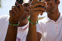 Two young men with wristbands holding mobile phones