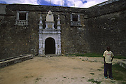 Man passes through Saint Sebastian Fortress gate. This gate is an example of the Manueline style, a late gothic style spread during Portuguese Discoveries