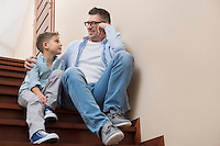 Full length of father and son looking at each other while sitting on steps at home