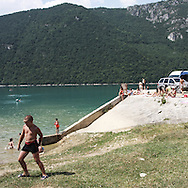 A child play on a lake. There are several arguments about the derivation of the name  &quot;Montenegro&quot;, one of these relates to dark and deep forests  that once covered the Dinaric Alps, as it was possible to see them from the sea. <br /> Mostly mountainous with 672180 habitants on an area of 13812 Km&sup2;, with a population density of  48 habitants/Km&sup2;. <br /> It borders with Bosnia, Serbia, Croatia, Kosovo and Albania but  Montenegro has always been alien to the bloody political events that characterized Eastern Europe in recent decades. <br /> From 3 June 2006, breaking away from Serbia, Montenegro became an independent state. <br /> In the balance between economy devoted to sheep farming and a shy tourist, mostly coming from Bosnia and Herzegovina, Montenegro looks to Europe with a largely unspoiled natural beauty. <br /> Several cities in Montenegro, as well as the park Durmitor, considered World Heritage by UNESCO but not yet officially because Montenegro has yet to ratify the World Heritage Convention of UNESCO.