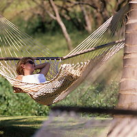 Hawaii, Molokai, female relaxing in hammock between two coconut trees