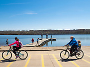 19 APRIL 2020 - DES MOINES, IOWA: People ride their bikes around Gray's Lake, a popular public park and lake south of downtown Des Moines. After a week of colder than normal weather, including three inches of snow, the weekend was spring like and people went to public parks to enjoy the pleasant weather.     PHOTO BY JACK KURTZ
