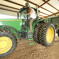 Justin Michael leaves his tractor after off loading trailer full of soybeans.