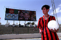SPECIAL OLYMPICS AFGHANISTAN..KABUL 24 August 2005..Ghazi Stadium...A disable athlete, wearing the Milan football-club's  Tshirt, stands next to the Afghan Olympics bill-board...On 23-25 August 2005, Special Olympics Afghanistan held its first national Games at Olympic Stadium in Kabul. More than 300 athletes, including 80 female athletes, experienced a taste of happiness and achievement for the first time in their lives. They competed in athletics, bocce and football (soccer). Because of cultural restrictions, males and females competed at separate venues.
