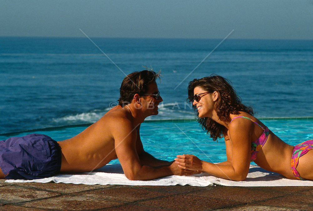couple laying down face to face at the ocean in Mexico
