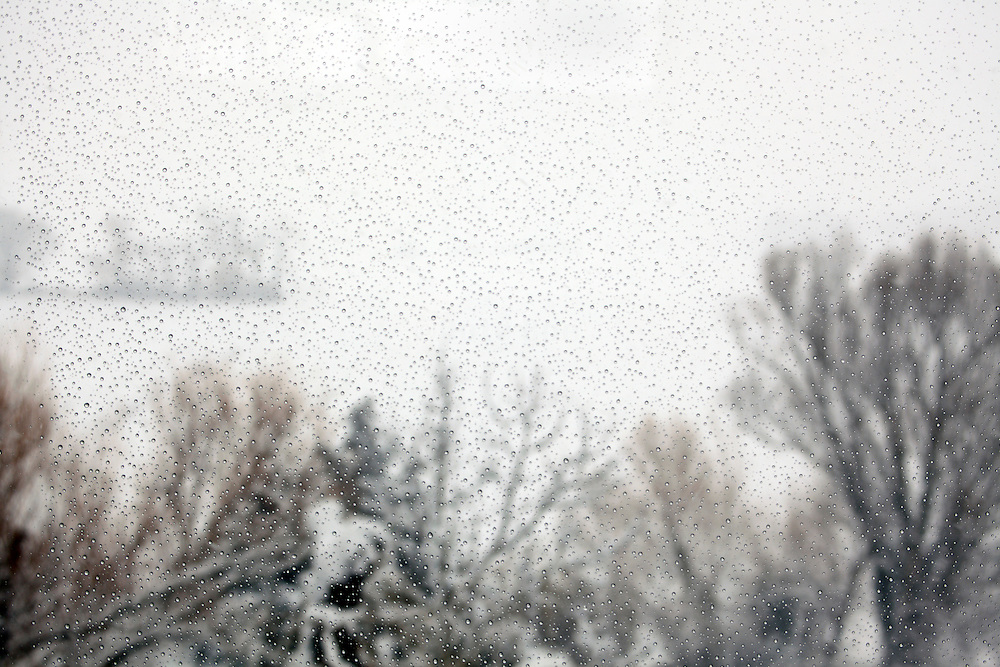 water drops on window looking towards a snow covered landscape with trees