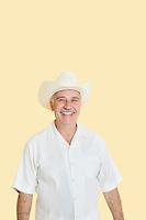 Portrait of happy senior man wearing cowboy hat over yellow background